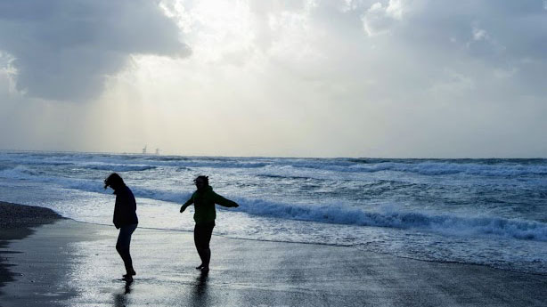 Two silhouetted students walking on the beach.