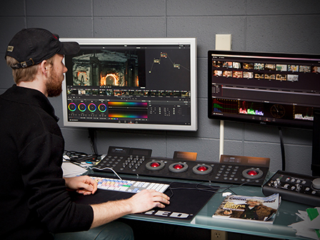 A filmmaking student uses DaVinci Resolve to do color grading in one of eight private editing suites.